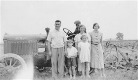 Photo:Henry Parcell with his wife Mabel (extreme right) and young David Milller and Doreen Kneller. Can you name the tractor driver and the second lady?